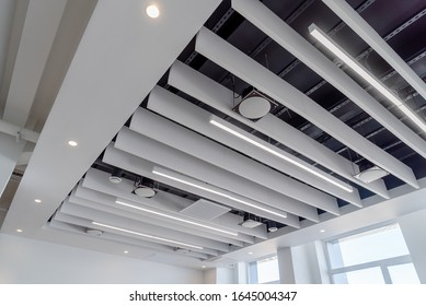 linear LED lights and sound absorbing ponies hang on a plasterboard ceiling with integrated spotlights