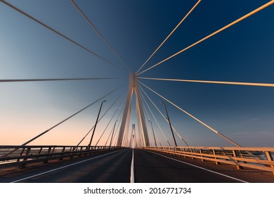 Linear perspective view of a white cable-stayed suspension bridge in the golden light of the rising sun shot from a ground level in horizontal (landscape) format
