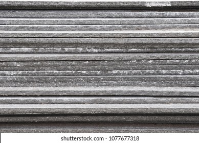 Linear texture of gray asbestos slate plates stacked on top of each other close-up side view