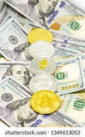 Lined up cryptocurrency coins displayed on a heap of one hundred dollar bills with focus on bitcon coin.