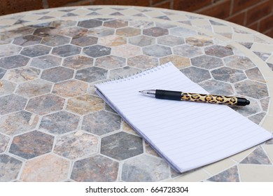 lined note book and patterned pen on a hexagon style ceramic outside table