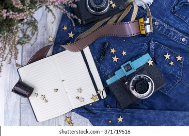 Lined notebook on the washed-out jeans and white wooden background. Accessories: wooden stars, heather twigs, photo camera and linen braided cord. Top view