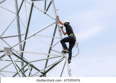 lineman climbing on transmission line tower