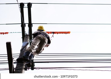 Lineman is using electrical insulating equipment (clamp stick) to dismantle conductor cover from high-voltage distribution systems that are still flowing.