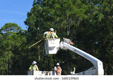 Linemen in a boom truck bucket repair downed power line in Panama City Fl. USA in the days after hurricane Michael Aug 24 2017