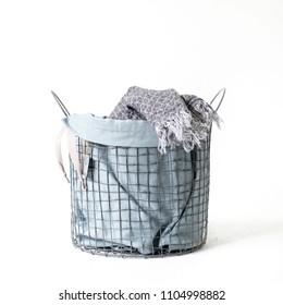 Linen drawstring bag full of laundry on white background.