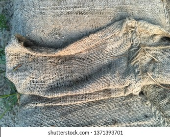 Linen folds on white stitched sandbags at the beach.
