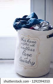 Linen laundry hamper or basket full of dirty laundry with a phrase on it THIS HOME IS FILLED WTH ENDLESS LOVE AND LAUNDRY
