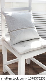 linen pillows on a white chair in the interior