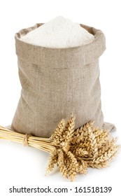 Linen sack full of flour and wheat spike isolated on white background
