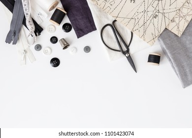 Linen textiles, scissors and sewing supplies on white desk