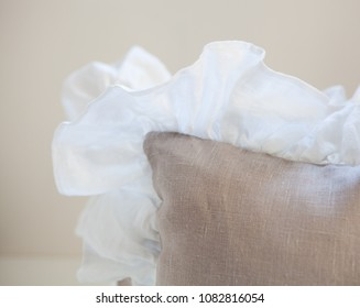 Linen throw pillow with white ruffles close up. Corner of pillow. Beige pillow with white ruffles.