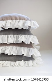 Linen throw pillows stack. Ruffled pillows in beige and gray.Pillows for home or bedding decor.