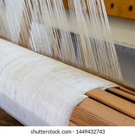 Linen yarn wound on the warp beam of a wooden hand weaving loom