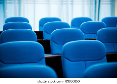 lines of blue theater chairs.