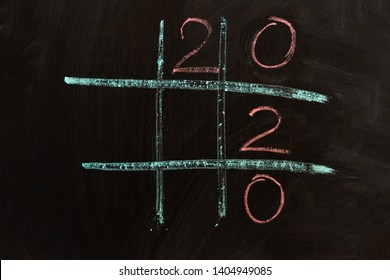 "lines drawn in green chalk on a black board form cells in which the numbers are drawn in pink ""2"", ""0"", ""2"", ""0"""
