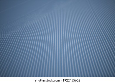 lines in groomed snow on cross country nordic or alpine ski terrain on cold wintery day at ski resort on winter morning in seasonal temperatures