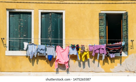 Lines of linen drying on ropes stretched outside colourful window facades in Venice, Italy