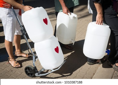 Lines of people waiting to collect natural spring water for drinking in Newlands with 25 litre bottles and wheel trolly in the drought in Cape Town South Africa