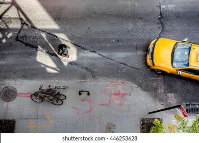 Lines and shadows of overhead view of New York City street scene with yellow taxi cab and pedestrian