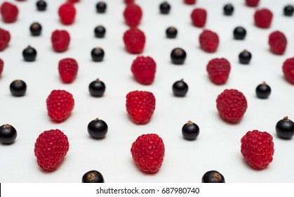 Lines from sweet fresh organic raspberries and blackberries, selective focus, free space. Fresh berries on white wooden background with blank space. Summer and healthy food concept