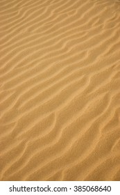 Lines in the yellow sand of a beach. Out of focus image.