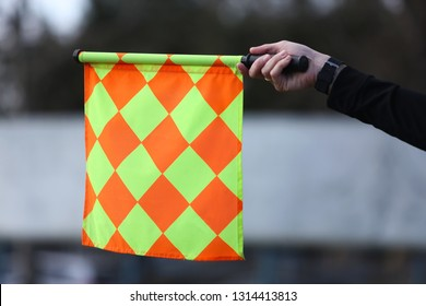 A Linesman signals for offside by raising his flag during a soccer match.
