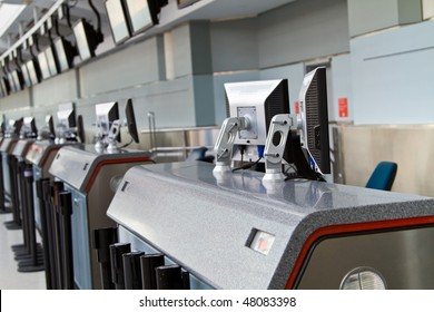 A lineup of check-in counters  with LCD screens, both on the counters and above, at Pearson International Airport, Toronto, Ontario, Canada.