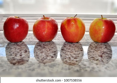 A lineup of fresh, pink lady apples reflects itself onto the black and white granite counter top. These ripe, red and gold apples are a delight to the palette.