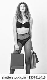 Lingerie boutique concept. Underwear or lingerie for female. Elite lingerie for sensual girl. Woman tousled hairstyle posing in black lingerie. Girl sexual temptress wear stockings hold shopping bags.