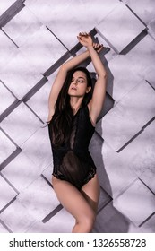 Lingerie campaign photography. Seductive alluring brunette supermodel with long down hair pouncing for a lingerie campaign in sexy lace bodysuit in photo studio