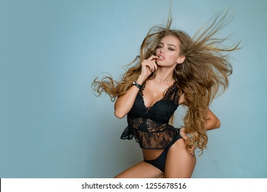 Lingerie model. Beautiful woman in black lingerie on copy space background. Sexy elegant woman posing in studio. With developing long curly hair. Sensual look. Lace lingerie underwear on fit body