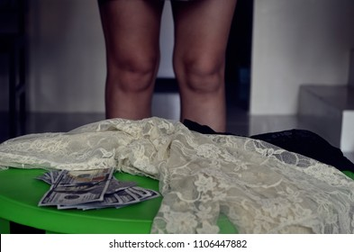 Lingerie and money on a table, sign of prostitution and human trafficking.