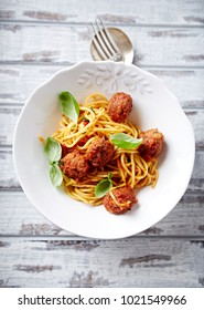 Linguine with meatballs, tomato sauce and basil leaves. Italian food. Italian cuisine. Symbolic image. Concept for a tasty and hearty dish. Rustic wooden background. Top view. Copy space.
