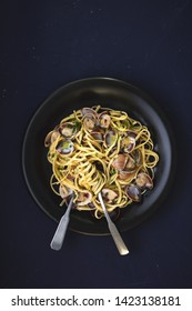 Linguine with white clams top view in dark plate. Fresh seafood pasta. Vongole.