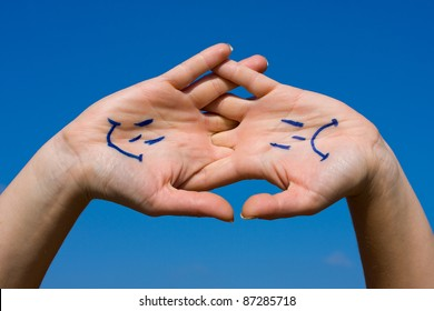 Linked hands with smiles and sadness pattern against the blue sky