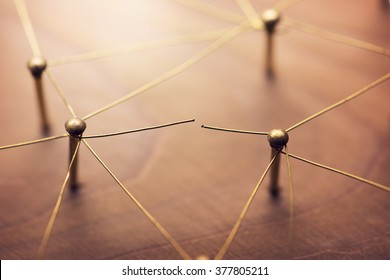 Linking entities. Broken connection or broken relation. Network, networking, social media, internet communication abstract. Web of gold wires on rustic wood.
