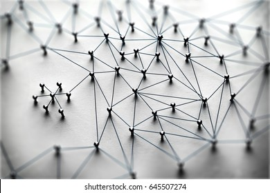 Linking entities. Monotone. Networking, social media, SNS, internet communication abstract. Small network connected to a larger network. Web of light to dark blue, wires on white background.