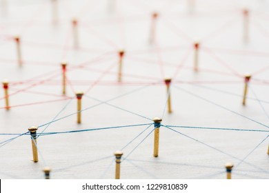 Linking entities. Network, networking, social media, internet communication abstract. A small network connected to a larger network. Web of gold wires on white wooden background. Network hub or key