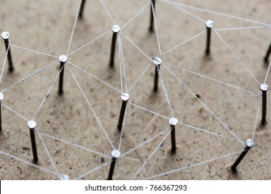 Linking entities. Network, networking, social media, connectivity, internet communication abstract. A small network connected to a larger network. Web of threads on cork board.
