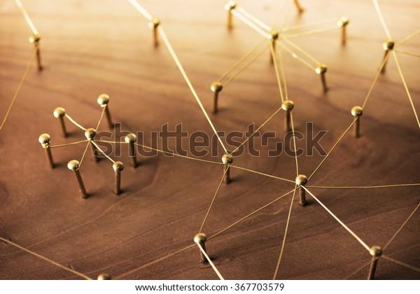 Collegamento di entità. Rete, networking, social media, comunicazione internet abstract. Una piccola rete connessa a una rete più grande. Rete di fili d'oro su legno rustico.