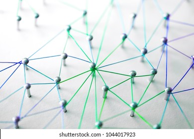Linking entities. Networking, social media, SNS, internet communication abstract. devices or people connected to a network. Web of green, blue and purple wires on white background. Shallow DOF.