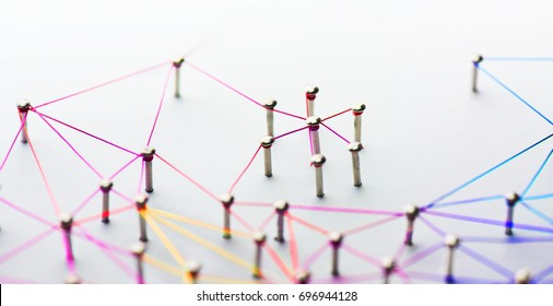 Linking entities. Networking, social media, SNS, internet communication abstract. Small network connected to a larger network. Web of red,orange yellow and blue wires on white background. Shallow DOF