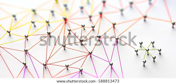 Linking entities. Networking, social media, SNS, internet communication abstract. Small network connected to a larger network. Web of red, orange and yellow wires on white background. Shallow DOF.
