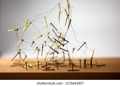 Linking entities. Uprooted or tangled network, social media, internet communication abstract. Web of gold wires on rustic wood.  Shallow Depth of field.