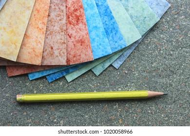 Linoleum. Arrangement of a multi-colored marble linoleum on a white wood texture. Building theme and presentation.
