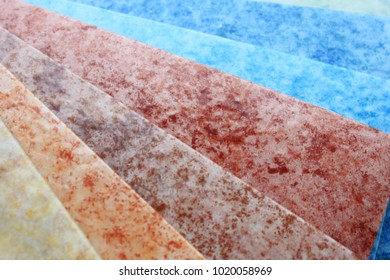 Linoleum. Arrangement of a multi-colored marble linoleum on a white wood texture. Building theme and presentation.