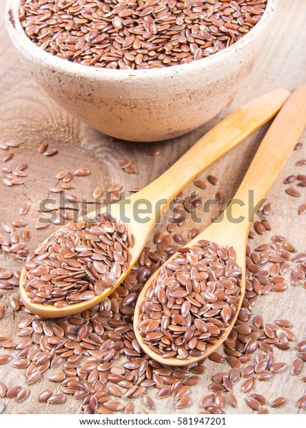 Linseed, flax seeds with spoon on wooden background - concept of healthy nutrition.