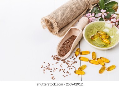 Linseed and flaxseed oil capsules over white wooden background with copy space