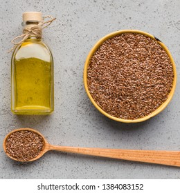 Linseed oil in bottle, bowl and spoon of linseeds on concrete background, top view. Healthy fats concept